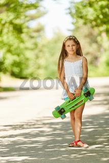 Mädchen steht mit einem Skateboard im Park