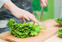 Close-up Female hands chopping a green plant salad cooking salad from vegetables on a wooden cutting board at home. The concept of vegetarianism and healthy lifestyles