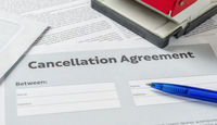 A Cancellation agreement with a pen on a desk