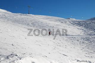 Skier downhill on snowy ski slope