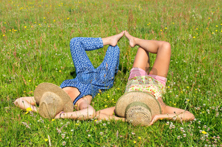 Two friends lying together in meadow