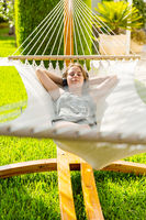 Girl relaxing and listening to music in hammock in the garden