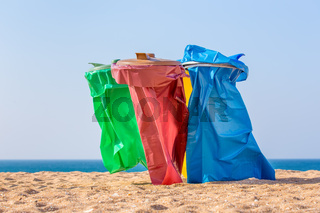 Colorful garbage bags on beach at coast