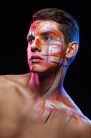 handsome young man with paint strokes on face