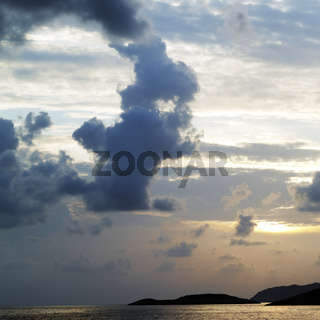Islands in sea and sky with clouds at sunset