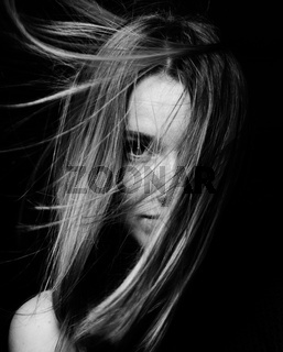 Portrait of a beautiful brunette girl with long hair in the studio