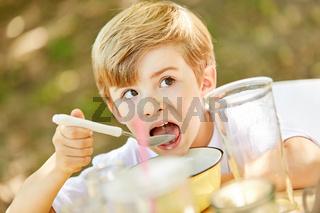 Hungriger Junge isst Müsli zum Frühstück