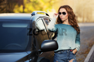 Young fashion woman in sunglasses standing next to her car outdoor