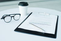 A pair of women's glasses and a pen lying on top of a white sheet of paper on wooden surface. The sheet has a coffee stain. Copy space in lower and right part of image. High angle view.
