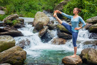 Woman doing Ashtanga Vinyasa Yoga asana outdoors at waterfall