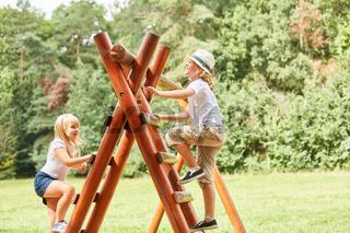 Zwei Kinder klettern auf ein Klettergerüst