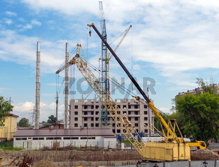 Tower cranes against blue sky, with clouds