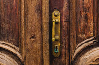 Vintage background. Brass-made old handle with Elements of an carved wooden door decorated with massive wooden simulating weaving. An old concept of old antiques. Varnished old mahogany