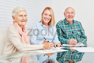 Frau und Senioren lösen Rätsel als Gedächtnistraining