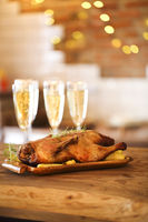 Winter holiday family dinner with roast poultry and champagne