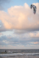Parachute surfing in the sea at dusk