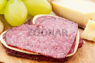 Heart sharped salami with mountain cheese and grapes as closeup on a chopping board