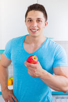 Gesunde Ernährung junger Mann Essen Apfel Frucht Obst in der Küche Hochformat