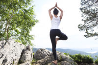 Attractive young woman doing a yoga pose for balance and stretching staying on top of high rock in the mountains