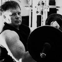 Schwarzweißaufnahme eines männlichen Kraftsportlers im Fitnessraum