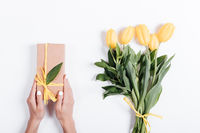 Female hands holding a box with a gift near a bouquet of yellow tulips