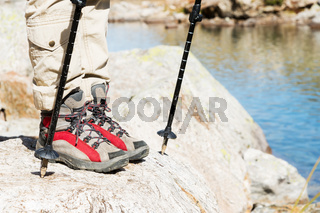 Close-up of female legs in trekking boots with sticks for Nordic walking against the background of rocks and distant Caucasian lands