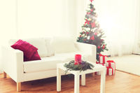 sofa, table and christmas tree with gifts at home