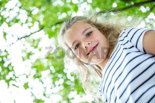 Blondes Mädchen lächelt im Frühling