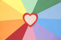 Red wooden heart on rainbow background