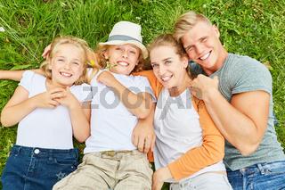 Familie kuschelt entspannt zusammen im Gras