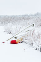 Red rowing boat on the beach in the reed with snow