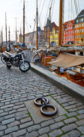 The motorcycle on the Nyhavn paving stone pavement in Copenhagen.