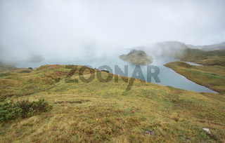 alpine lake in dense autumn fog
