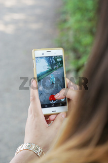 girl playing Pokemon Go on her smartphone