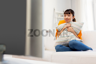 stunned asian woman with watching tv at home