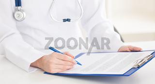 Doctor writing on sheet in clipboard