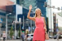 happy young woman waving hand on city street