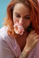 beautiful girl holding a pink ranunculus flower