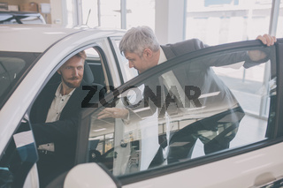 Vehicle dealer showing new car to young handsome man.