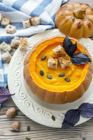 Pumpkin soup with croutons in a pumpkin.