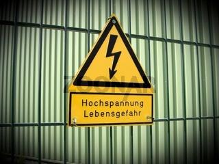 Gelbes Warnschild vor Hochspannung an einem Sicherheitszaun