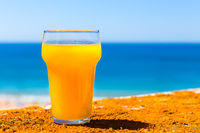 Glass filled with orange juice at sea