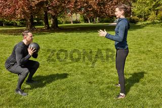 Mann trainiert mit Fitnessball bei Personal Trainer