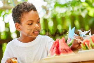 Junge auf einer Party dekoriert Wassermelonen