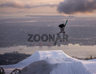 Freestyle skier performs backflip mute grab on jump above city
