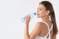 Woman drinking water from blue bottle