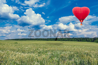 Red hot air balloon in the shape of a heart above the summer meadow.