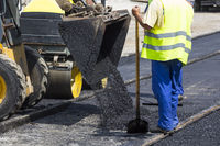 Worker construct asphalt road and railroad lines