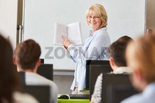 Frau als Dozentin erklärt den Lehrstoff