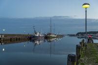 An der Mole liegende Schiffe im nächtlichen Hafen.